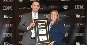 Patrick O'Leary (left) and Tara Bodine from UniFirst accept the Leadership 500 Excellence Award for the UniFirst Management Institute development program.