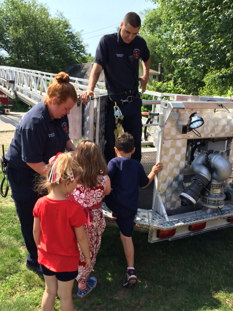 Children from the Tiny Tots/Kids Club program explore the bucket from the  Engine 1 Ladder Truck with the assistance of Firefighter Sullivan and Firefighter Newhall.