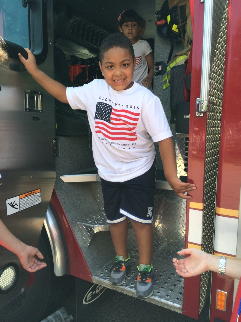 Aiden Harris from the Tiny Tots/Kids Club program explores the Wilmington Engine 1 Ladder Truck.
