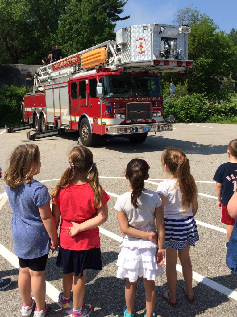 Children from the Tiny Tots/Kids Club program listen to the Wilmington Firefighters explain how the ladder truck operates.